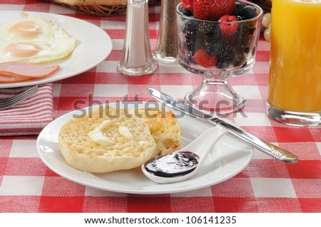 A buttered English muffin with orange juice and a fruit cocktail of fresh berries - stock photo