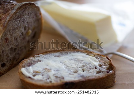 A buttered slice of cranberry walnut bread - stock photo