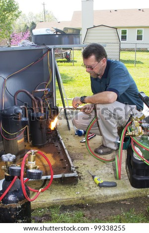 A/c  repair man, replacing condenser coils & compressor on residential air conditioning unit - stock photo