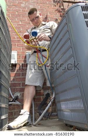 A/c tech charging air conditioning units, temperatures have set records this summer - stock photo