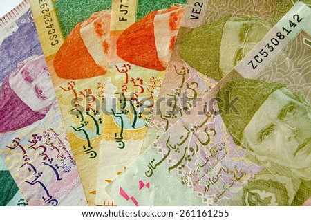 A cab of Pakistan rupee banknotes of different denominations.  The Father of the Nation - Muhammad Ali Jinnah shown wearing a hat known as a karakul. Used banknotes, less than 80% displayed. - stock photo
