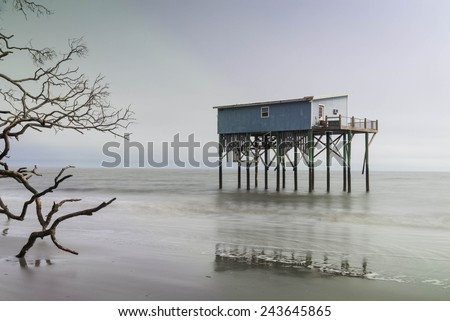 A cabin still stands where there used to be land on Hunting Island State Park in Beaufort, South Carolina - stock photo