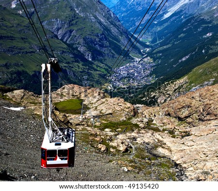 A cable car in the swiss alps with a valley below - stock photo