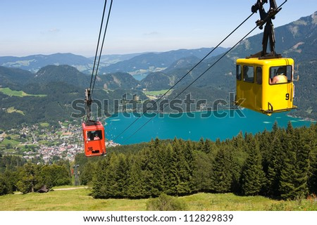 A cableway is bringing tourists up the zwolferhorn mountain near the city of st.Gilgen in Austria - stock photo