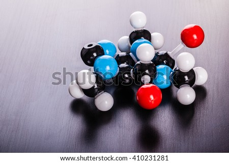 a caffeine chemical molecular structure model on a wooden surface - stock photo