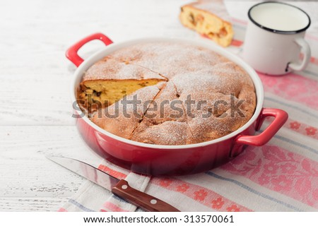 A cake with apples and raisins on wooden background. - stock photo