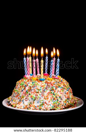 a cake with many coloured candles before black background - stock photo