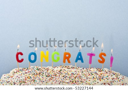 a cake with white frosting and sprinkles decorated with candles spelling out congrats - stock photo