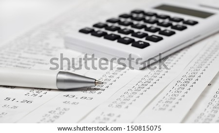 A calculator, a pen, bills, receipts - stock photo