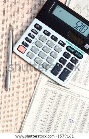 A calculator and a pen on top of a financial newspaper. - stock photo