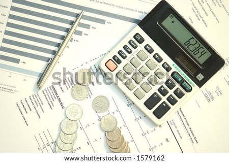 A calculator and a pen on top of financial documents. - stock photo