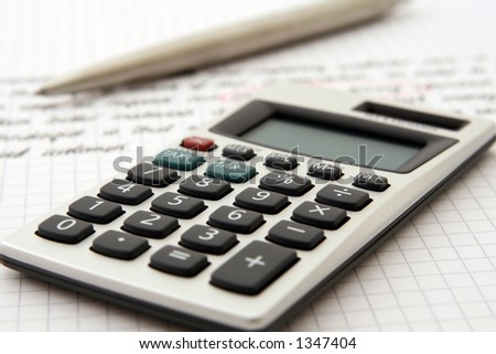 A calculator and pen indicate use by a professional for business purposes. - stock photo