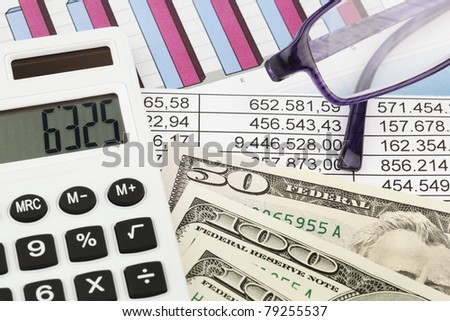 A calculator and various statistics in the calculation of balance sheet, revenue and profit. - stock photo