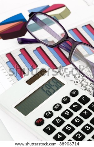 a calculator and various statistics when calculating the balance sheet, revenue and profit. - stock photo