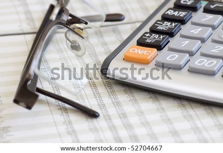 A calculator, glasses, and financial statement. Selective focus. - stock photo
