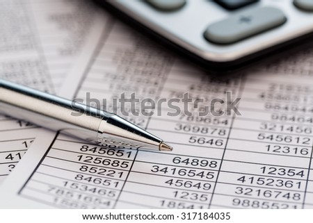 a calculator is located on the numbers a balance us statistics. photo icon for sales, profits and costs. - stock photo