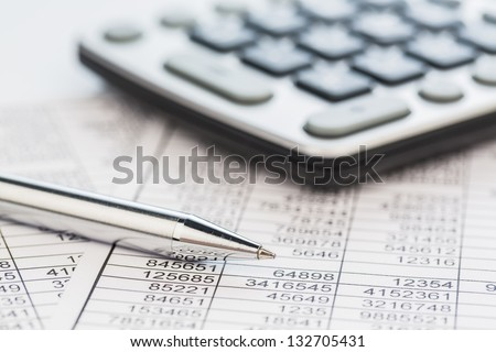a calculator is on a balance sheet numbers are statistics. photo icon for sales, profit and cost. - stock photo