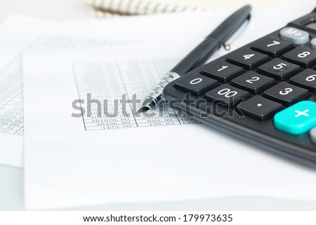 a calculator next to pen and financial documents, abstract accounting concept  - stock photo