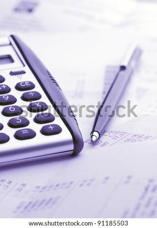 A calculator, pen, and financial statement. Blue tone - stock photo