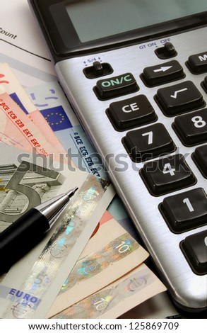 A calculator with euro notes and a pen - stock photo