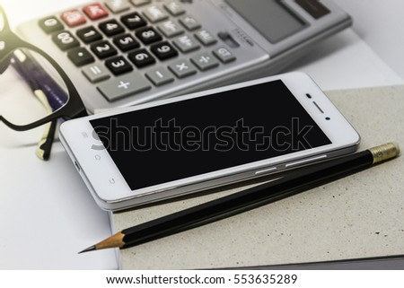 A calcutor, a smart phone, eye glasses and some stationery isolated on white background, top view with copy space - financial background concept