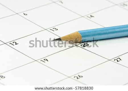 a calendar and a sharp blue lead pencil - stock photo