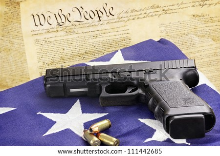 A 45 caliber handgun and ammunition resting on a folded flag against the United States constitution.
