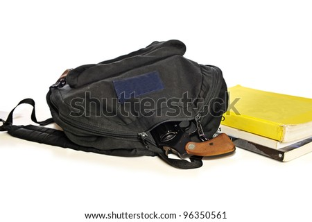 A 38 caliber pistol sticks out from a child's school book-bag in front of school textbooks, isolated on white, focus on gun handle - stock photo