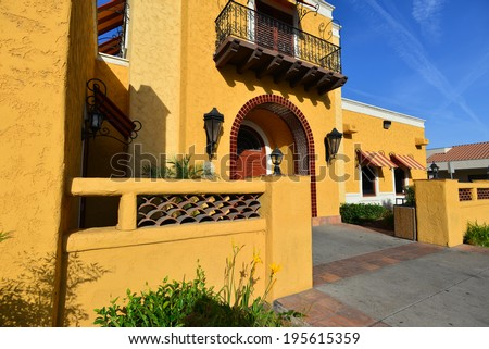A California building shows a strong Mexican or Spanish architectural influence with warm, bold colors. - stock photo