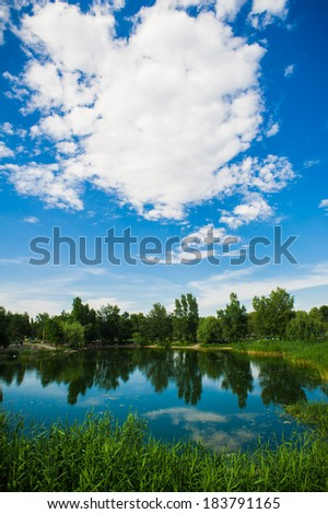 A calm evening landscape with lake and clouds. Green summer meadow and pond with blue cloudy sky - stock photo
