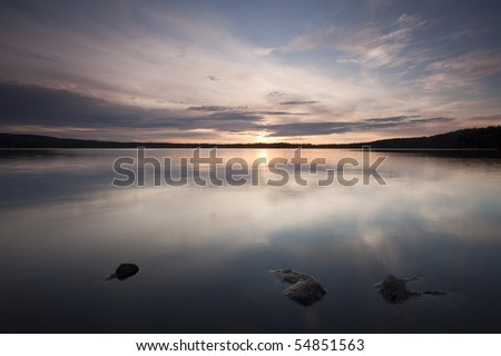 A calm lake. The clouds are reflecting on the surface. - stock photo