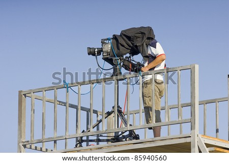 a cameraman filming a football game on a stadium profiled in a blue sky - stock photo