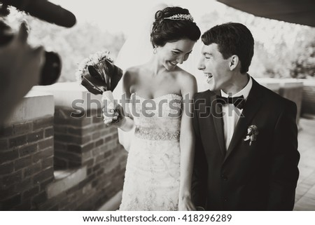 A cameraman shoot a smiling wedding couple