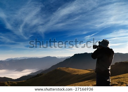 A cameraman standed and shot with clouds in the outdoor. - stock photo