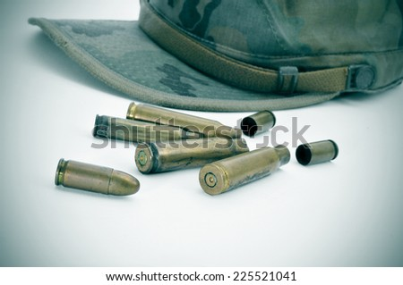a camouflage cap and some bullets and bullet shells - stock photo