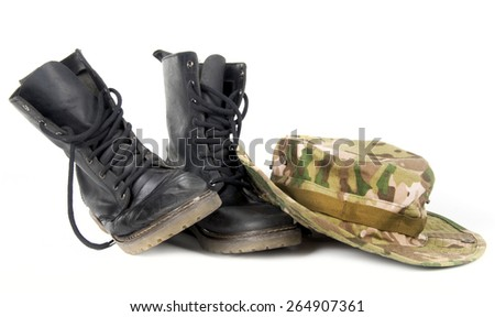 A camouflage hat resting on a pair of combat boots. - stock photo