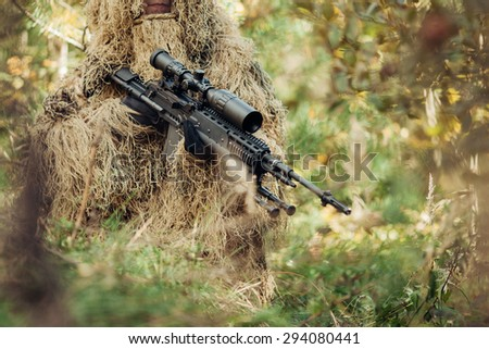 A camouflaged sniper with a rifle sitting in the woods waiting - stock photo