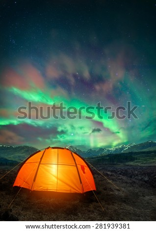 A camping tent glowing under the Northern Lights. Night time camping scene. - stock photo