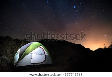 A camping tent glows under a night sky full of stars. Outdoor Camping adventure. - stock photo