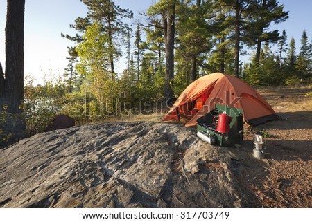 A campsite with an orange tent and cook stove in the north woods of Minnesota - stock photo