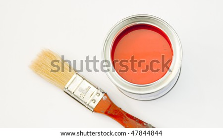 A can of bright red paint with a paint brush