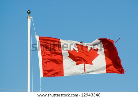 A canadian flag shot against a blue cloudless sky