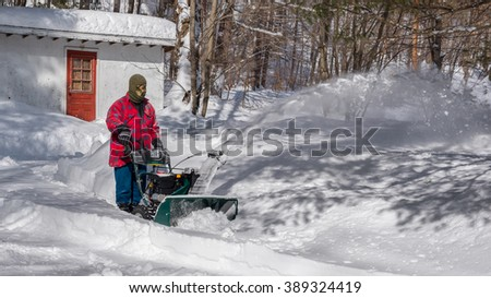 A Canadian man using a snow throwing machine on a winter day after a snowstorm dumped 8 inches of snow.  Man operating a snow blower in Canada.