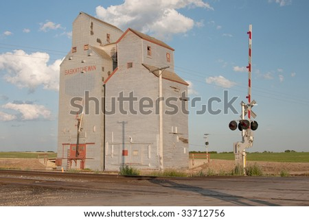 A Canadian prairie grain elevator in central Saskatchewan near a railroad crossing. - stock photo
