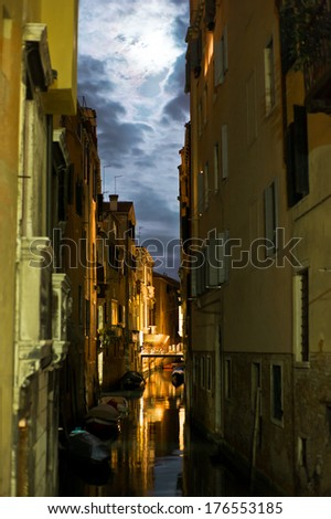 A canal running between tall buildings with a cloudy sky. - stock photo