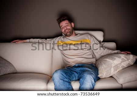 A candid photo of a man watching something funny on TV. No fake, cheesy smiles. - stock photo