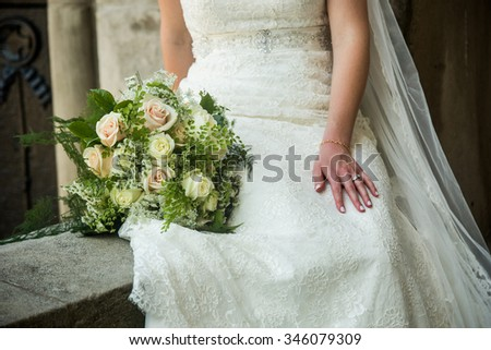 A candid photo of the bride holding a gorgeous bouquet. White and pink roses with baby's breath and green accents.
