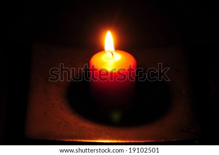 a candle burns bright extending from the shadow