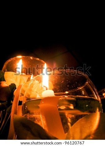 A candle floats in a wine goblet as a wedding centerpiece - stock photo
