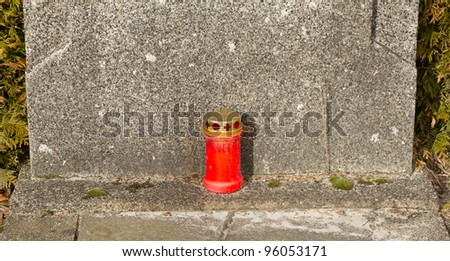 A candle for remebrance on an old grave in Holland - stock photo